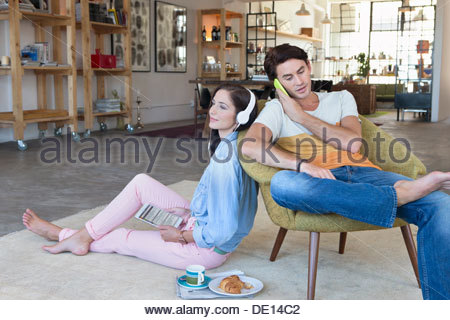 Couple using cell phone, headphones and digital tablet in livingroom - Stock Photo