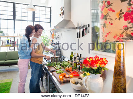 Couple cooking at stove in kitchen - Stock Photo