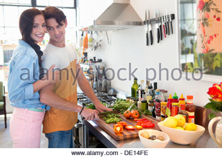 Portrait of smiling couple cooking in kitchen - Stock Photo
