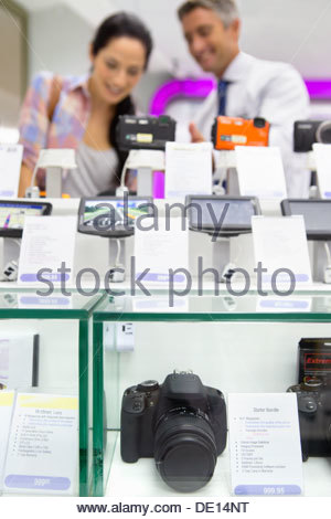 Salesman showing woman digital cameras in electronics store - Stock Photo