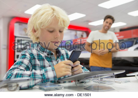 Close up of boy looking at cell phone in electronics store - Stock Photo