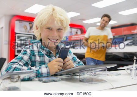 Portrait of smiling boy holding cell phone in electronics store - Stock Photo