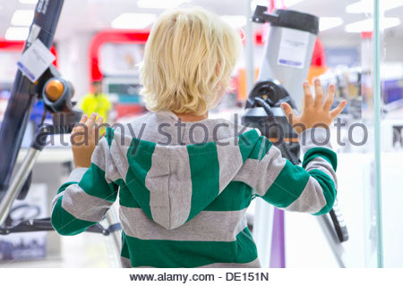 Boy looking at telescopes in window of electronics store - Stock Photo