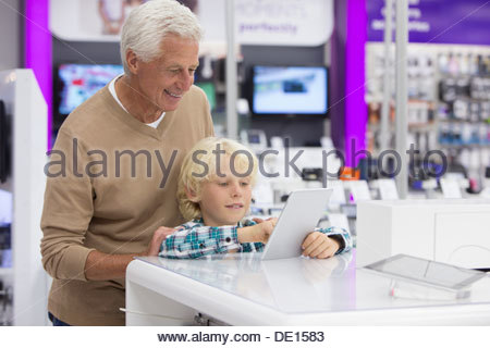 Grandfather watching grandson play with digital tablet in electronics store - Stock Photo