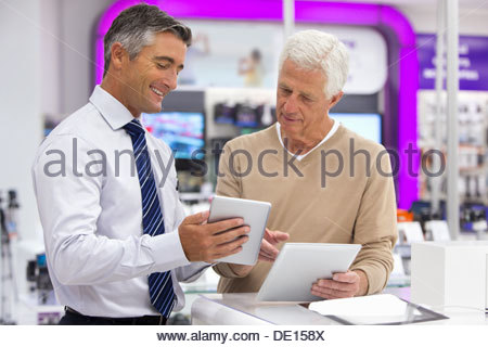 Smiling salesman showing senior man digital tablets in electronics store - Stock Photo