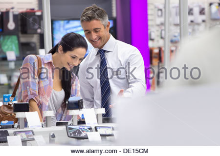 Smiling salesman showing woman digital cameras in electronics store - Stock Photo