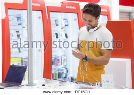 Smiling man looking at cell phone in electronics store - Stock Photo