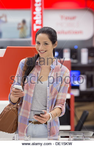 Portrait of smiling woman looking at cell phones in electronics store - Stock Photo