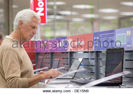 Senior man looking at prices on laptops in electronics store - Stock Photo
