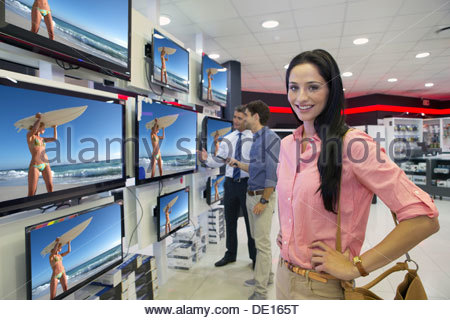 Portrait of smiling woman looking at flat screen televisions in electronics store - Stock Photo