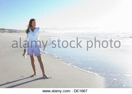 Woman standing on sunny beach - Stock Photo