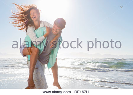 Man piggybacking enthusiastic woman on sunny beach - Stock Photo