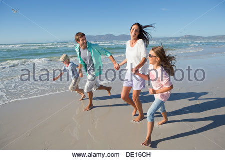 Happy family holding hands and running on sunny beach - Stock Photo