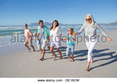 Happy multi-generation family holding hands and walking on sunny beach - Stock Photo