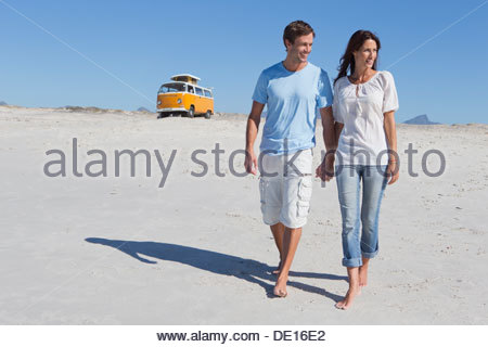 Couple holding hands and walking on beach with van in background - Stock Photo