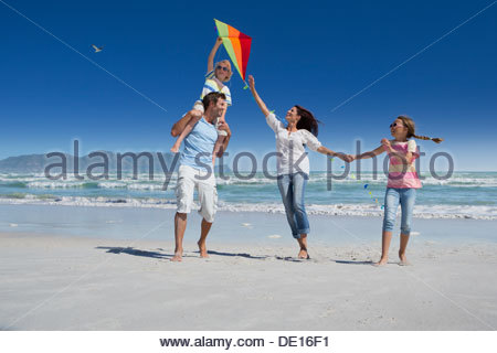 Happy family flying kite on sunny beach - Stock Photo