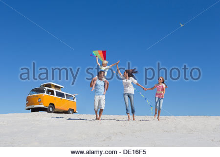Happy family flying kite on sunny beach with van in background - Stock Photo
