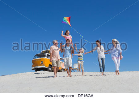 Happy multi-generation family walking with kite on sunny beach with van in background - Stock Photo