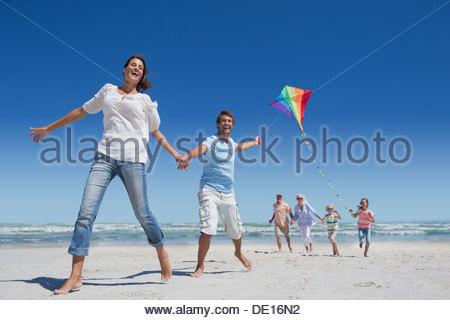 Happy family with kite running on sunny beach - Stock Photo