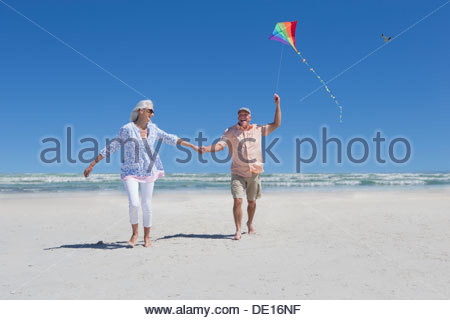 Happy senior couple holding hands and flying kite on sunny beach - Stock Photo