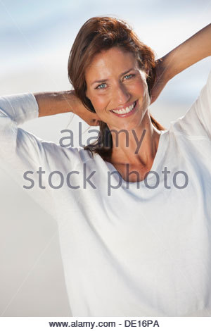 Portrait of smiling woman with hands behind head on beach - Stock Photo