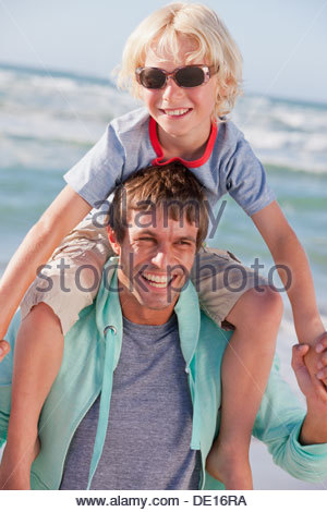 Father carrying son on shoulders at beach - Stock Photo