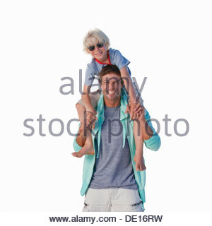 Portrait of smiling father carrying son on shoulders - Stock Photo