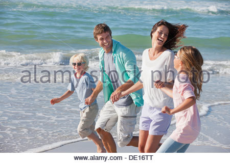 Happy family holding hands running on sunny beach - Stock Photo