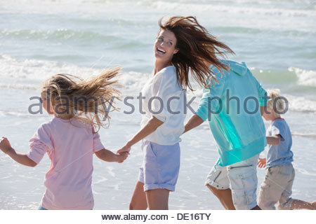 Happy family holding hands and running on beach - Stock Photo