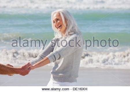 Senior couple holding hands on sunny beach - Stock Photo