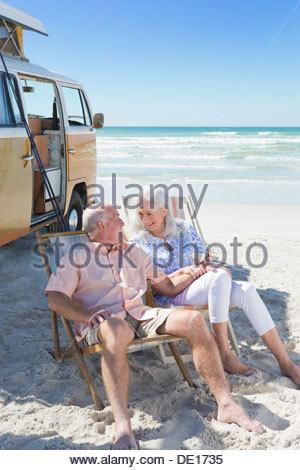 Happy senior couple sitting in lounge chairs on sunny beach near van - Stock Photo