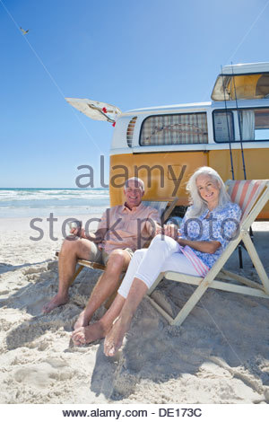 Portrait of smiling senior couple sitting on lounge chairs on sunny beach near van - Stock Photo