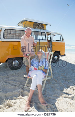 Senior couple drinking coffee on beach outside van - Stock Photo