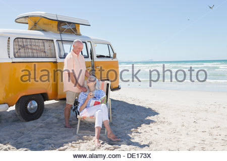 Senior couple relaxing outside van on sunny beach - Stock Photo