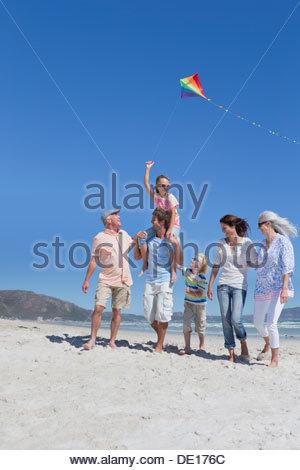 Happy multi-generation family with kite walking on sunny beach - Stock Photo