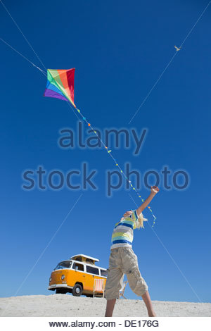 Boy flying kite on sunny beach with van in background - Stock Photo