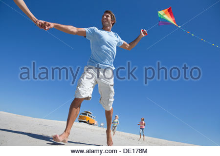 Happy family with kite on sunny beach with van in background - Stock Photo