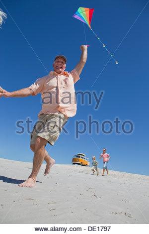 Portrait of smiling senior man with kite on sunny beach - Stock Photo