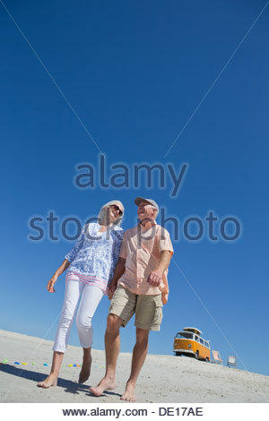 Happy senior couple walking on sunny beach with van in background - Stock Photo