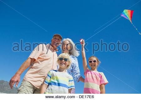 Portrait of happy grandparents and grandchildren flying kite against blue sky - Stock Photo