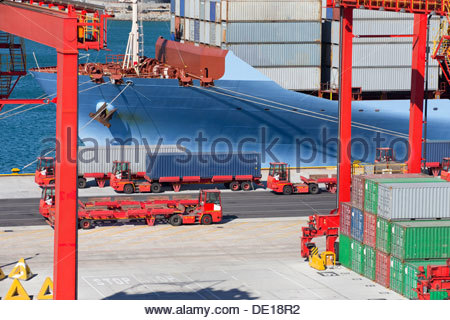 Trucks next to container ship with cargo containers at commercial dock - Stock Photo