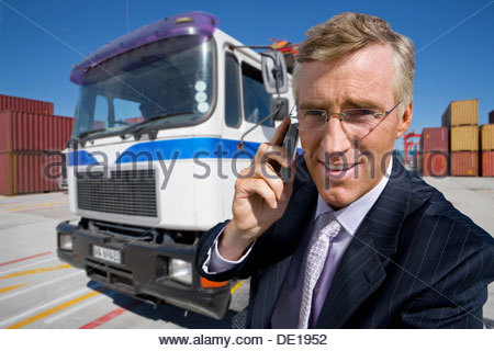 Portrait of smiling businessman talking on cell phone next to truck at commercial dock - Stock Photo