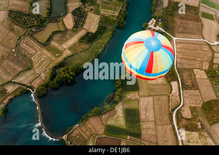 Close-up of colorful striped top of hot air balloon floating over Li river and farm fields viewed from higher hot - Stock Photo