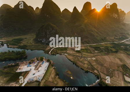 Sunset over karst peaks at road's end and ferry terminal in Li river valley from a hot air balloon - Stock Photo