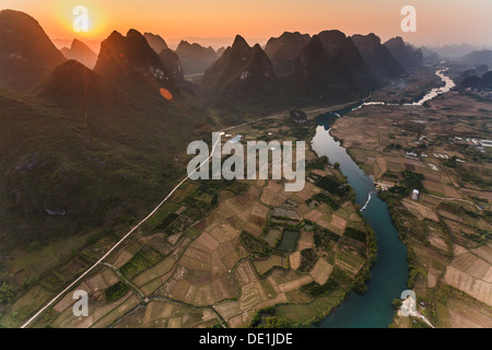 Sun sets between karst mountain peaks defining row of rugged edges in a long aerial view of the Li River Valley - Stock Photo