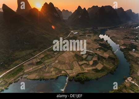 Golden sunset over karst peaks and cultivated fields of Li River valley in Yangshuo China from hot air balloon - Stock Photo