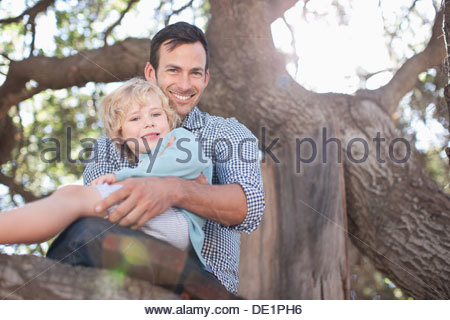 Father and son sitting in tree - Stock Photo