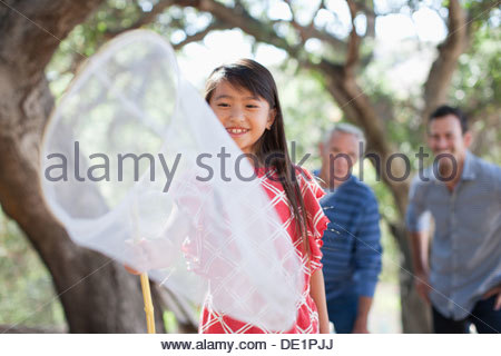 Smiling girl playing with butterfly net - Stock Photo