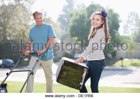 Father and daughter mowing lawn together - Stock Photo
