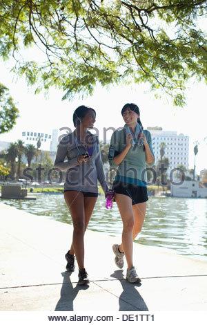Women walking along lake in park - Stock Photo